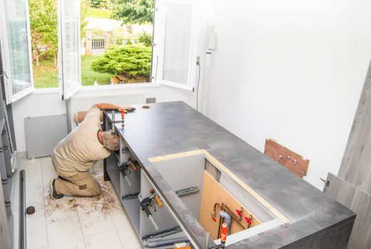 Fitter, manual construction worker man, installing integrated kitchen furniture with clamps and plumbing in a new kitchen custom made with opened window.